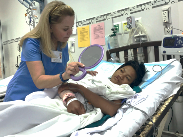 Tina Cerruti, Recovery Nurse, shows Bon, our first patient of the trip, his repaired cleft lip